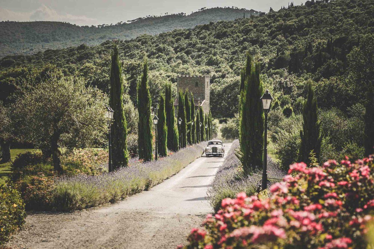 Garden villa wedding Italy. Bride and groom's entrance at villa Baroncino along the cypress path in a Bentley.