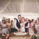 Marquee Wedding Ideas. Bride and groom cutting of the cake inside the marquee.