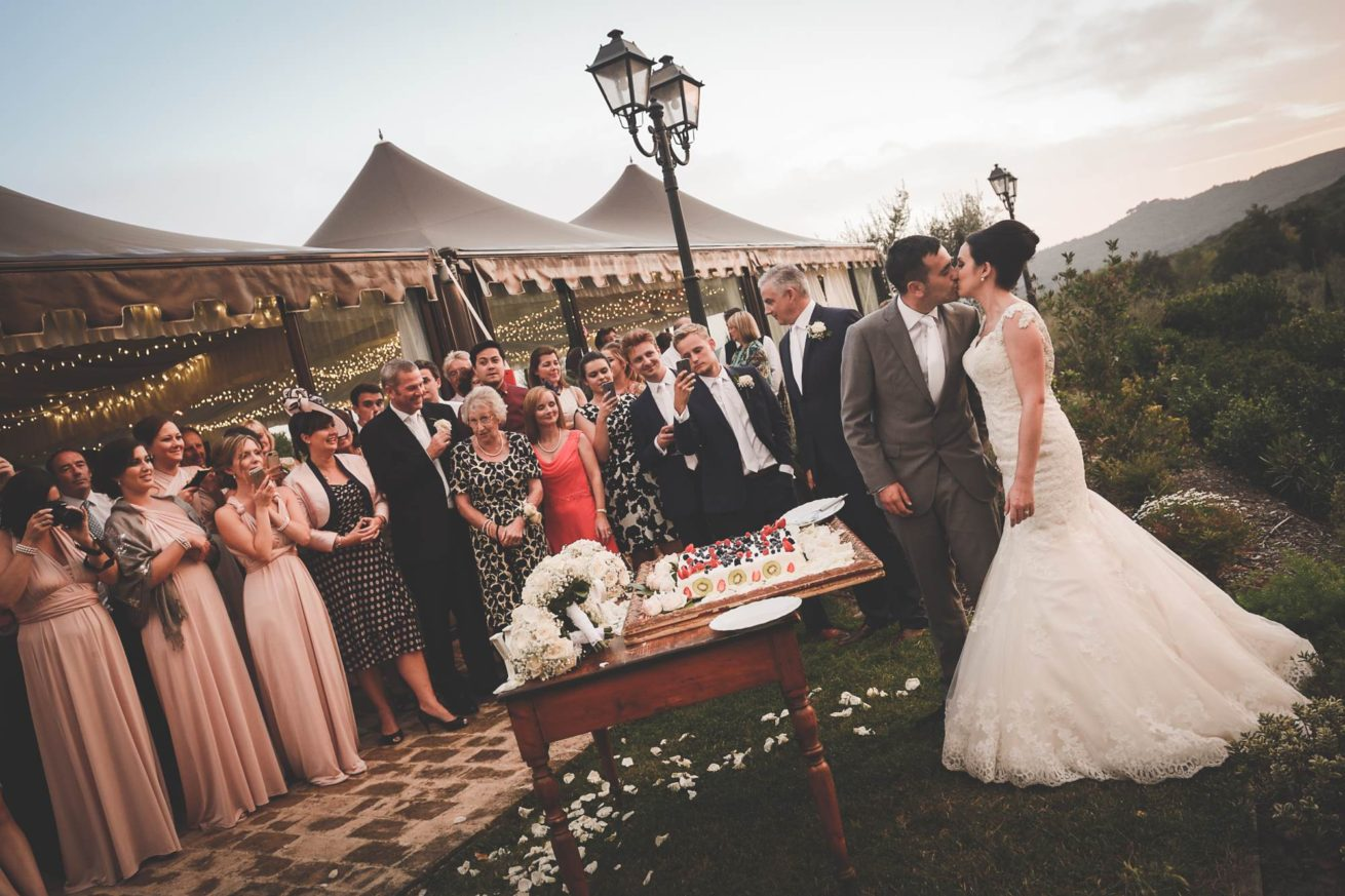Marquee Wedding Ideas. Bride and groom cutting of the cake outside the marquee.