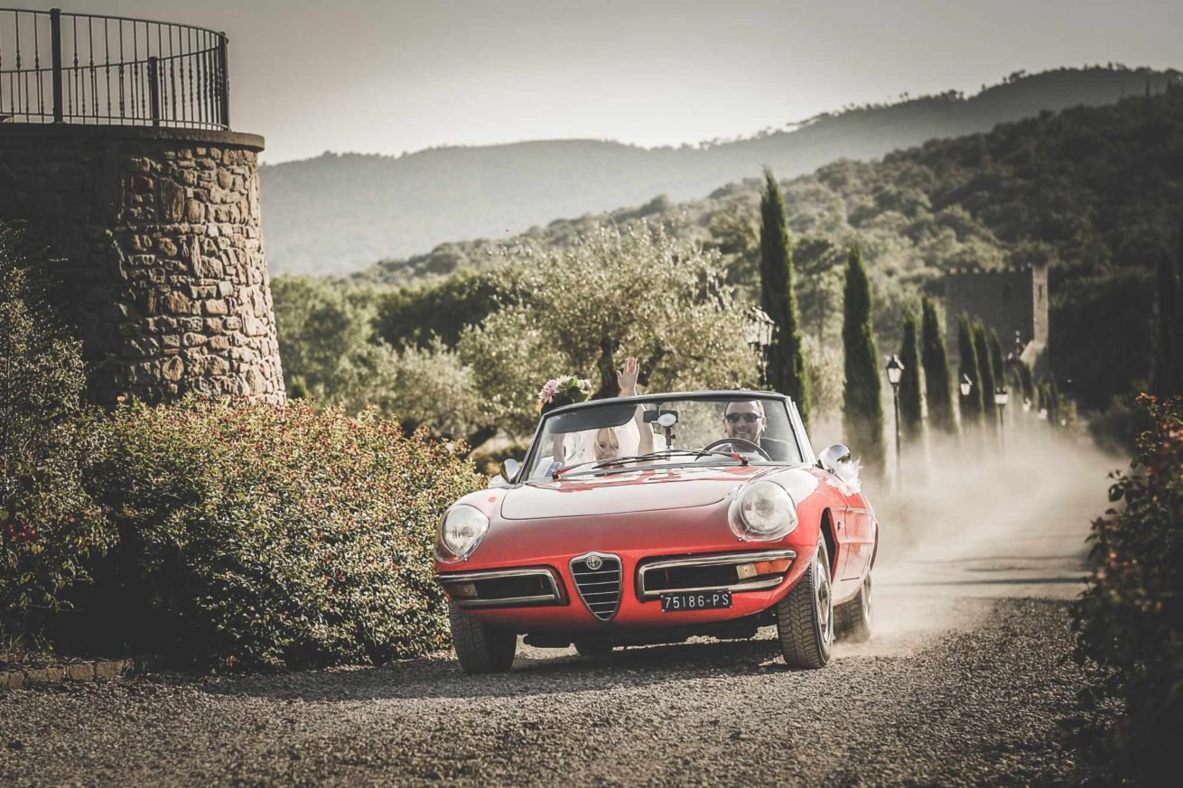 Garden villa wedding Italy. Bride and groom's entrance at villa Baroncino along the cypress path in a convertible red Alfa Romeo.